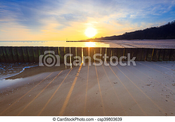 sunset on the beach with a wooden breakwater, long exposure - csp39803639