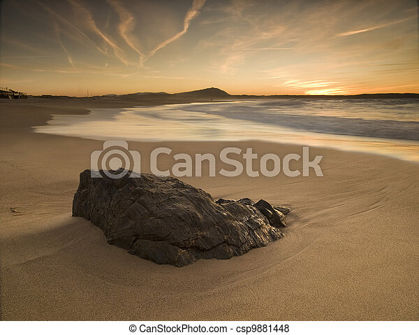Sunset on the beach with rock in the foreground - csp9881448
