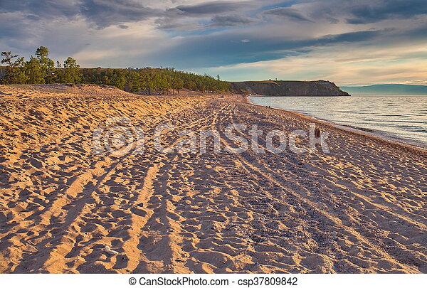 Sunset on the island of Olkhon, Lake Baikal shore. - csp37809842