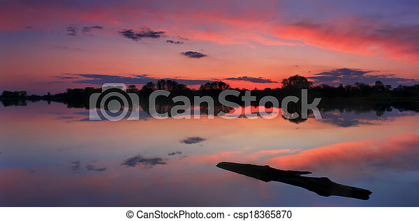 Sunset on the shore of a lake - csp18365870