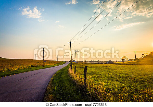 Sunset over a country road and farm fields near Hanover, Pennsylvania. - csp17723618