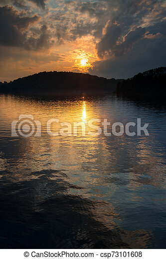 Sunset over a lake in summer - csp73101608