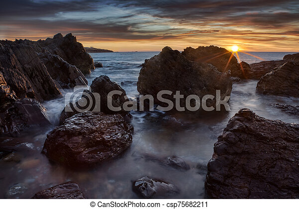 Sunset over a rocky beach in Australia - csp75682211