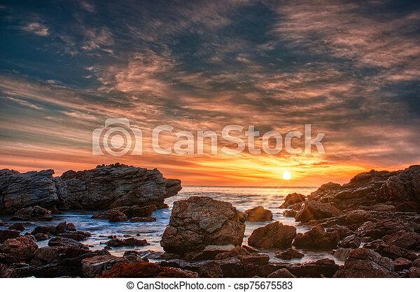 Sunset over a rocky beach in Australia - csp75675583