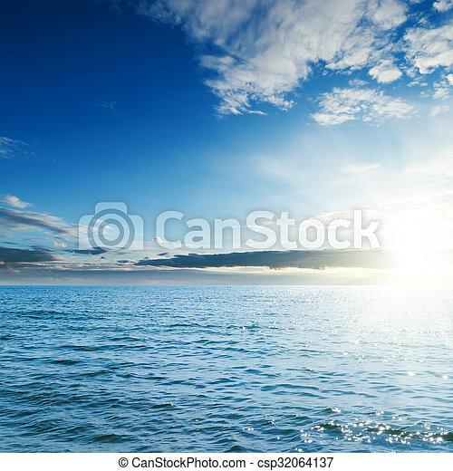 sunset over blue sea - csp32064137