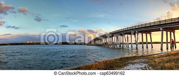 Sunset over Bridge along Estero Boulevard, crossing over New Pass from Estero Bay in Bonita Springs - csp63499162