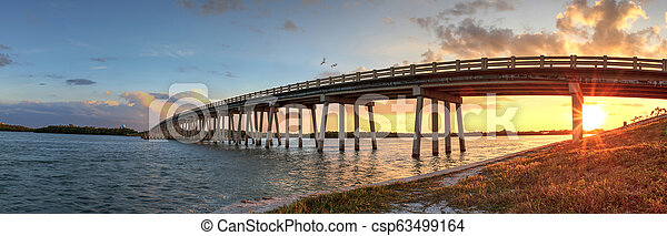 Sunset over Bridge along Estero Boulevard, crossing over New Pass from Estero Bay in Bonita Springs - csp63499164