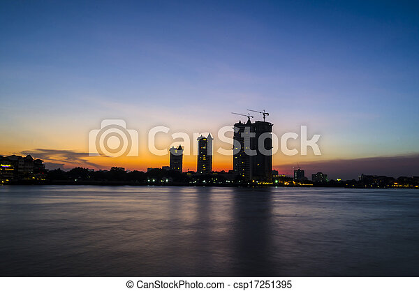 sunset over bridge and river in city - csp17251395