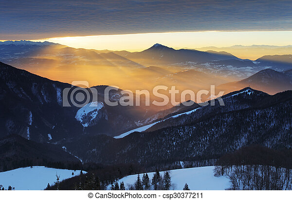 Sunset over color mountain silhouette with rays - csp30377211