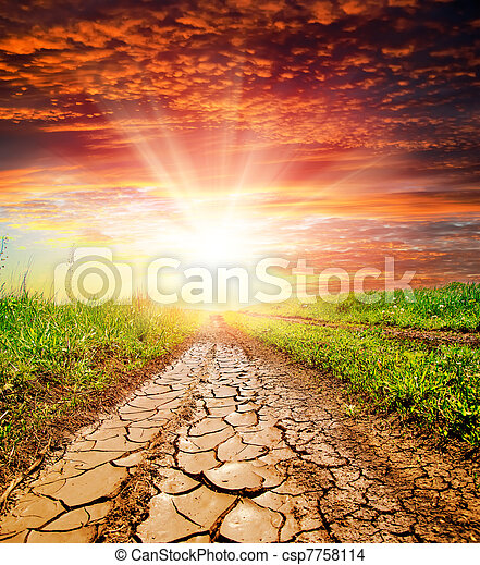 sunset over cracked rural road in green grass and cloudy sky - csp7758114