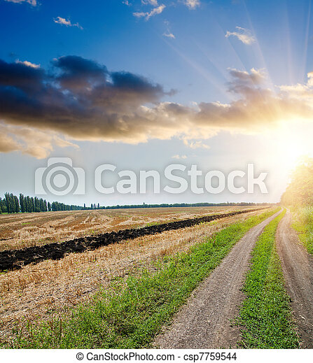 sunset over field and rural road with dramatic sky - csp7759544