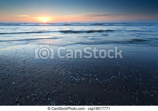 sunset over sand beach at low tide on North sea - csp19017771