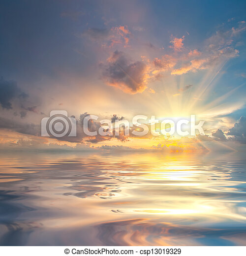 Sunset over sea with reflection in water - csp13019329