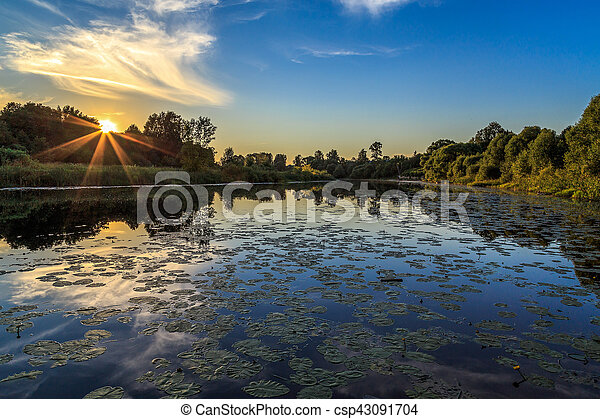 Sunset over the river, evening hot day - csp43091704