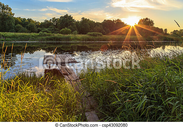 Sunset over the river, wooden bridge - csp43092080
