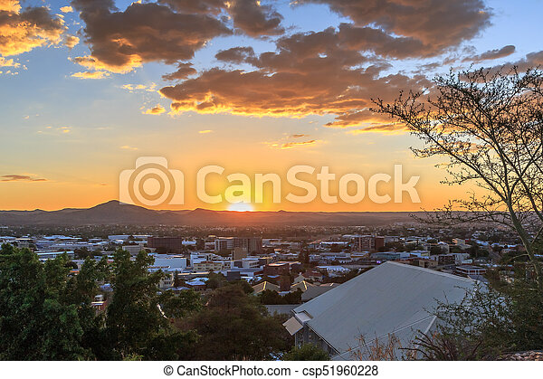 Sunset over Windhoek Central Business district with sun and mountains in the background, Windhoek, Namibia - csp51960228