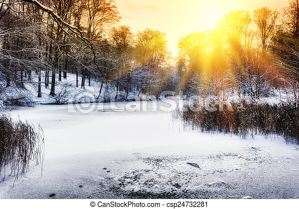 Sunset over winter forest lake - csp24732281