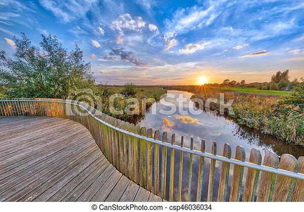 Sunset over Wooden Balustrade on bridge - csp46036034