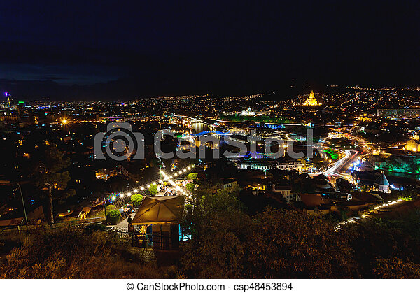 Sunset panorama view of Tbilisi, capital of Georgia country, from Narikala  fortress  Famous landmarks with illumination  Tourists have dinner in