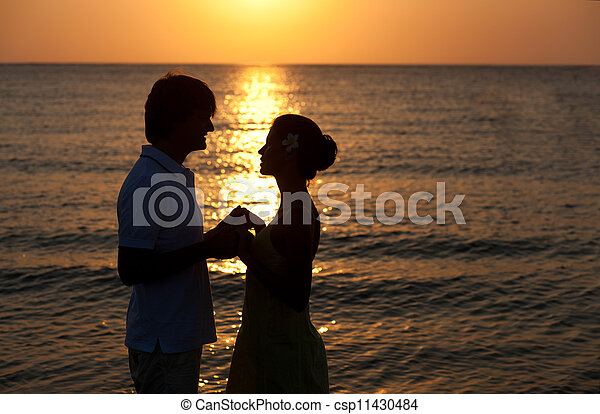 sunset silhouette of happy young lovers on the beach. honeymoon - csp11430484