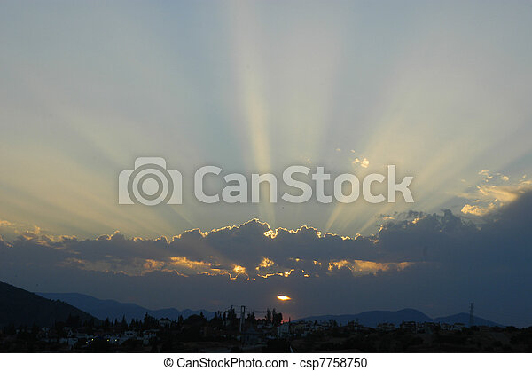 Sunset with clouds illuminated by the sun to the light, divine sunshine - csp7758750