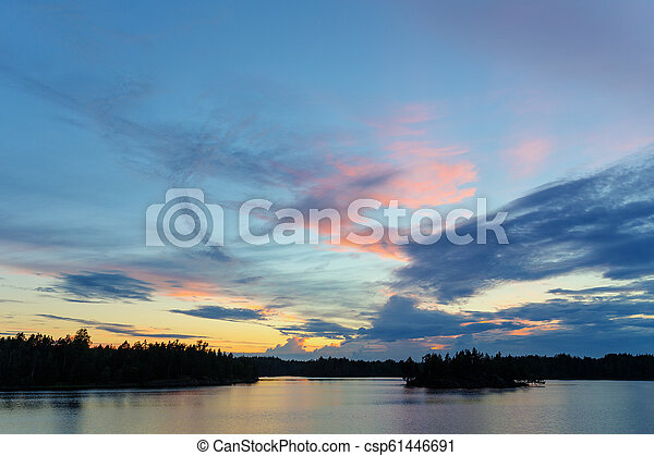 sunset with clouds over the forest lake - csp61446691