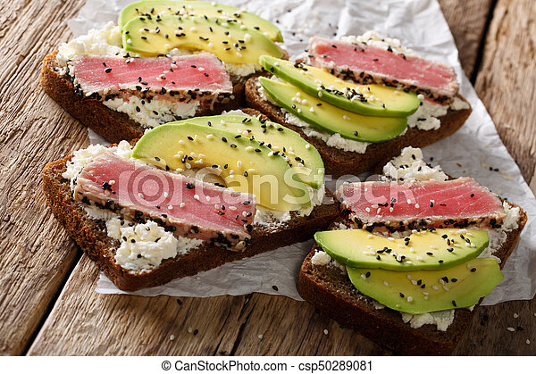 Super food: sandwiches with tuna steak in sesame, avocado and cottage cheese close-up. Horizontal - csp50289081