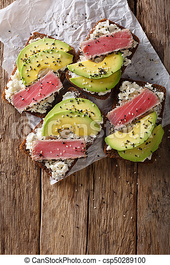Super food: sandwiches with tuna steak in sesame, avocado and cottage cheese close-up. Vertical top view - csp50289100
