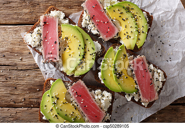 Super food: sandwiches with tuna steak in sesame, avocado and cottage cheese close-up. Horizontal top view - csp50289105