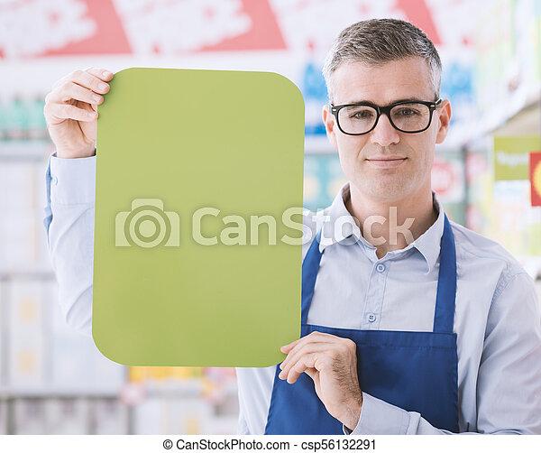 Supermarket clerk holding a sign - csp56132291