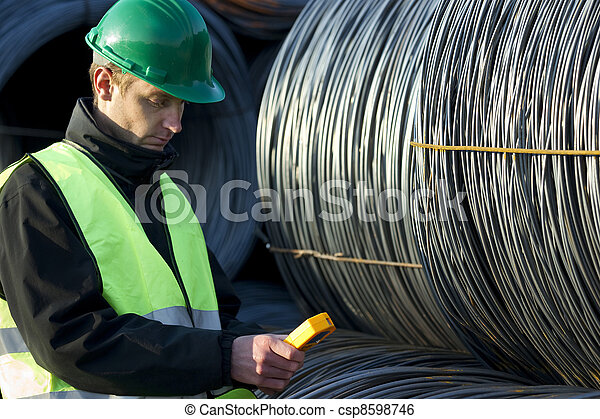 Supervisor Looking At Geiger Counter With Cable Wire Rolls - csp8598746