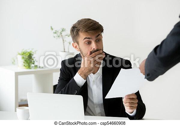 Surprised confused caucasian employee receiving dismissal notice - csp54660908