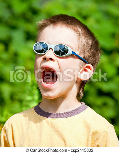4e5382a1b597 Surprised kid. Young boy wearing sunglasses open-mouthed with surprise.