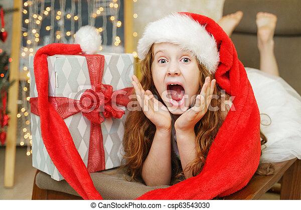 Surprised little girl in Santa hat. Christmas concept. - csp63543030