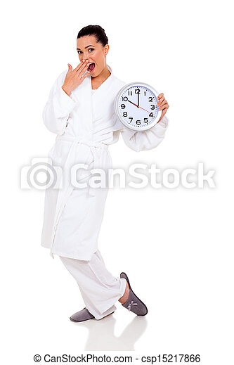 surprised young woman in pajamas with clock - csp15217866