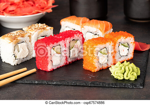 Sushi rolls and sashimi in a black stone plate. - csp67574886