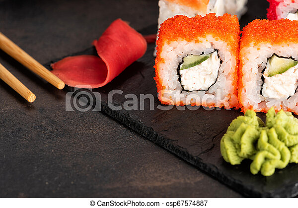 Sushi rolls and sashimi in a black stone plate. - csp67574887