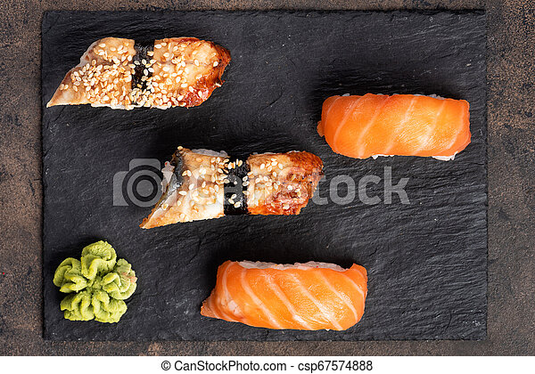 Sushi rolls and sashimi in a black stone plate. - csp67574888