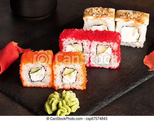 Sushi rolls and sashimi in a black stone plate. - csp67574843