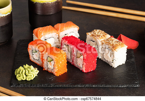 Sushi rolls and sashimi in a black stone plate. - csp67574844