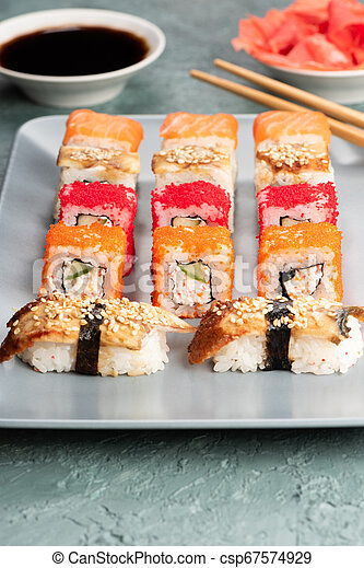 Sushi rolls and sashimi in a black stone plate. - csp67574929