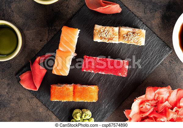 Sushi rolls and sashimi in a black stone plate. - csp67574890