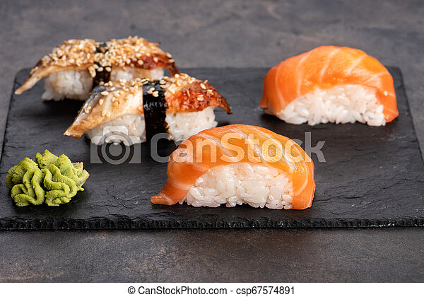 Sushi rolls and sashimi in a black stone plate. - csp67574891
