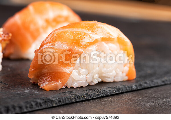 Sushi rolls and sashimi in a black stone plate. - csp67574892