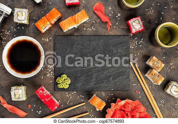 Sushi rolls and sashimi in a black stone plate. - csp67574893