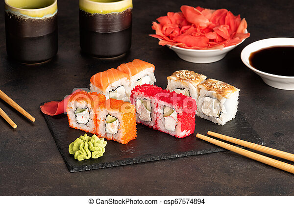 Sushi rolls and sashimi in a black stone plate. - csp67574894