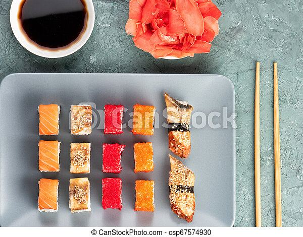 Sushi rolls and sashimi in a black stone plate. - csp67574930