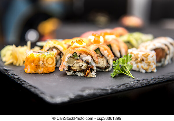 Sushi rolls on a black plate - csp38861399