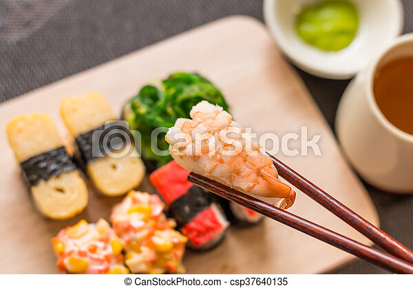 Sushi set with chop sticks, wasabi served on wooden slate, selective focus - Sushi is food originating in Japan, consisting of cooked vinegar rice combined with other ingredients such as vegetables - csp37640135