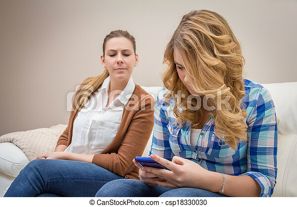 Suspicious mother spying a daughter looking phone - csp18330030